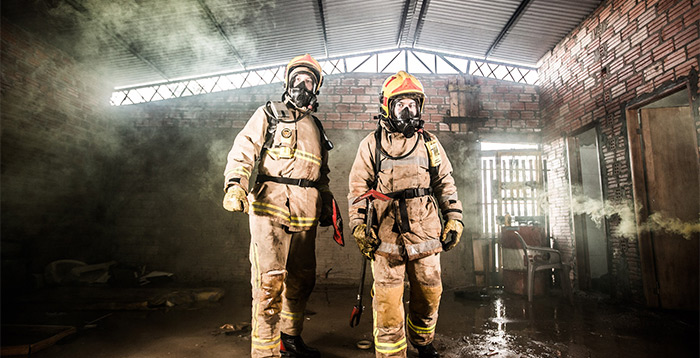 Firefighters in recently extinguished building