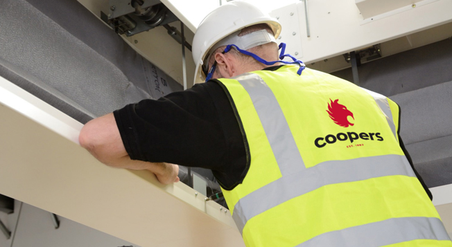 Coopers Fire Service Engineer fixing a FireMaster Concertina Fire Curtain