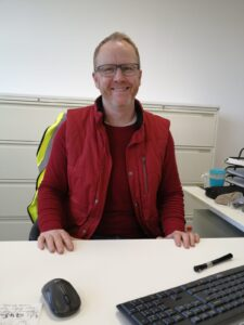 Man wearing all red sat at his desk